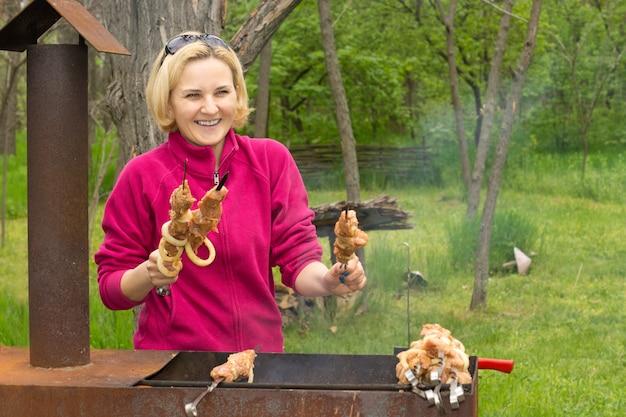 Gelukkig aantrekkelijke blonde vrouw koken op een bbq