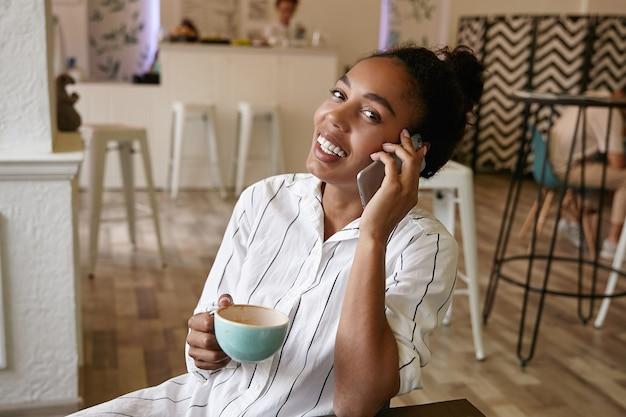 Gelukkig aantrekkelijke donkere vrouw met broodje kapsel praten aan de telefoon met vriend tijdens het drinken van koffie in café, vrolijk op zoek
