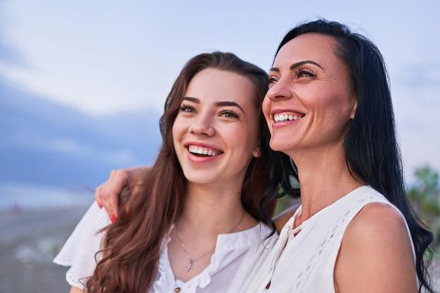 Gelukkig aantrekkelijke glimlachende dochter knuffelen met lachende moeder en plezier samen buitenshuis