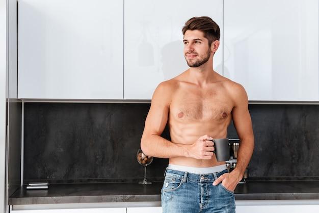 Gelukkig aantrekkelijke jonge man koffie drinken op de keuken thuis