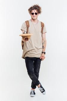 Gelukkig aantrekkelijke jonge man met hoed en om geld te vragen op witte achtergrond