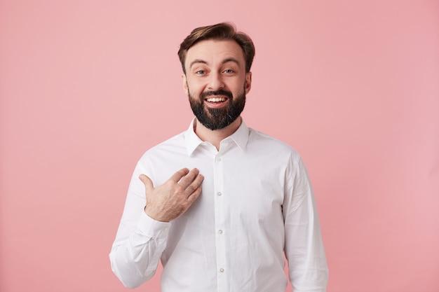 Gelukkig aantrekkelijke jonge ongeschoren brunette man met trendy kapsel die gelukkig op zichzelf toont en vreugdevol naar voren kijkt, gekleed in een wit overhemd terwijl hij tegen een roze muur staat