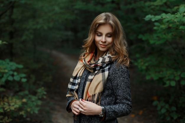 Gelukkig aantrekkelijke jonge vrouw in een modieuze grijze jas met een stijlvolle geruite sjaal staat op een pad in het bos in de buurt van groene bomen