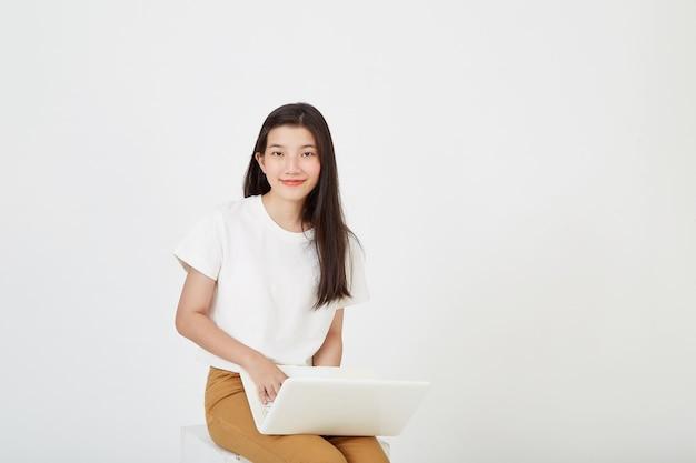 Gelukkig aantrekkelijke jonge vrouw met laptopcomputer kleermakerszit en kijken naar lege ruimte op witte studio achtergrond Premium Foto