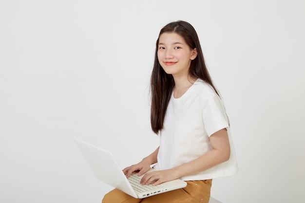 Gelukkig aantrekkelijke jonge vrouw met laptopcomputer kleermakerszit en kijken naar lege ruimte op witte studio achtergrond
