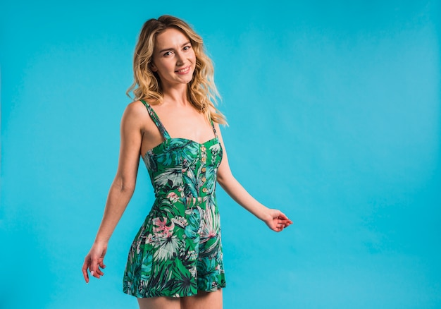 Gelukkig aantrekkelijke jonge vrouw poseren in bloemrijke jurk