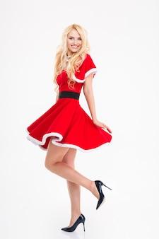 Gelukkig aantrekkelijke jonge vrouw poseren in rode kerstman kostuum geïsoleerd op witte achtergrond