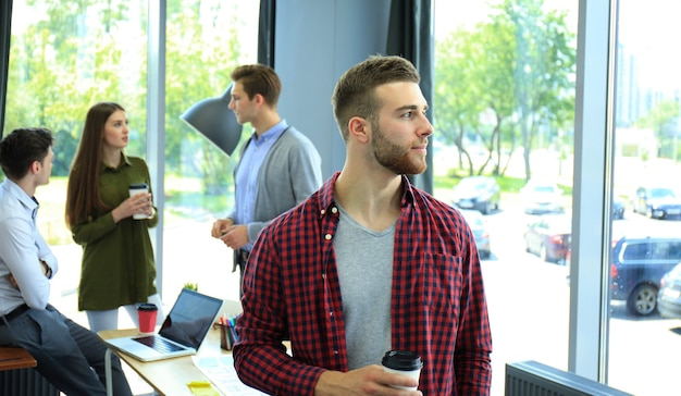 Gelukkig aantrekkelijke jonge zakenman koffie drinken op kantoor.
