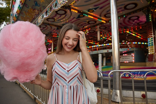 Gelukkig aantrekkelijke jongedame met lang bruin haar lichte jurk met riemen dragen, staande boven pretpark met roze suikerspin in de hand, voorhoofd met gesloten ogen aanraken en breed glimlachend