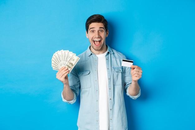 Gelukkig aantrekkelijke man die verbaasd kijkt, met contant geld en creditcard, concept van banken, krediet en financiën. blauwe studioachtergrond.