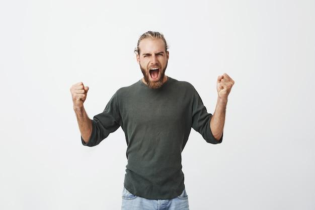 Gelukkig aantrekkelijke man met baard luid schreeuwen en expressief gebaren met handen
