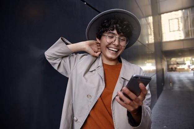 Gelukkig aantrekkelijke modieuze dame met kort kapsel trendy kleding, brillen en brede grijze hoed dragen, mobiele telefoon vasthouden en scherm gelukkig met brede glimlach kijken