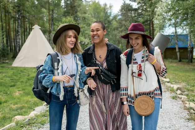 Gelukkig aantrekkelijke multi-etnische meisjes chatten en lachen tijdens het wandelen over de camping