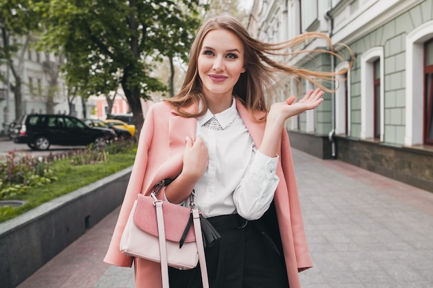 Gelukkig aantrekkelijke stijlvolle lachende vrouw lopen stad straat in roze jas lente modetrend bedrijf portemonnee, elegante stijl, lang haar zwaaien