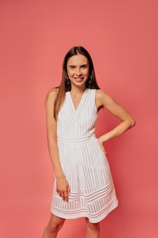 Gelukkig aantrekkelijke stijlvolle vrouw, gekleed in witte jurk poseren over roze muur tijdens fotoshoot in de studio