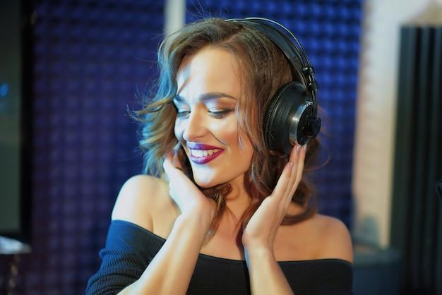 Gelukkig aantrekkelijke zangeres met haar handen op de koptelefoon luisteren naar muziek