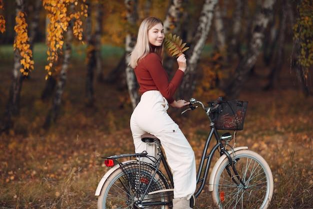 Gelukkig actieve jonge vrouw fietsten in herfst park