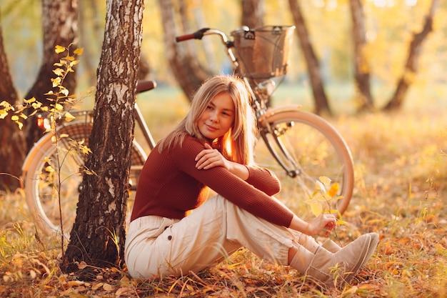 Gelukkig actieve jonge vrouw vintage fiets in herfst park bij zonsondergang