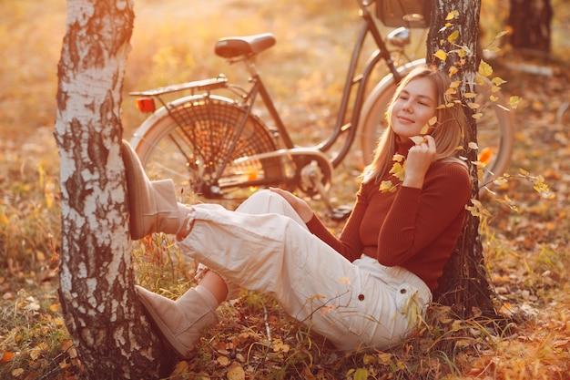 Gelukkig actieve jonge vrouw zitten met vintage fiets in herfst park bij zonsondergang