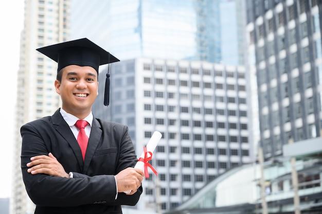 Gelukkig afgestudeerd. gelukkige aziatische mens die in graduatietoga diploma op stedelijke stad in hand houden.