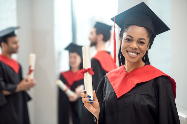 Gelukkig afgestudeerd. leuk afrikaans amerikaans meisje in baret dat gelukkig kijkt en keurig glimlacht