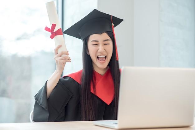 Gelukkig afgestudeerd. leuke aziatische glimlachende gediplomeerde die haar diploma houdt en gelukkig kijkt