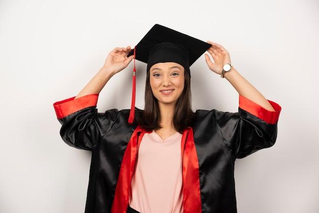 Gelukkig afgestudeerde student in jurk poseren op witte achtergrond.