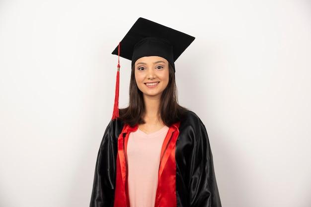 Gelukkig afgestudeerde student in jurk staande op een witte achtergrond.
