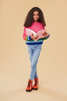 Gelukkig afrikaans amerikaans meisje dat in vrijetijdskleding en een leerboek glimlacht houdt