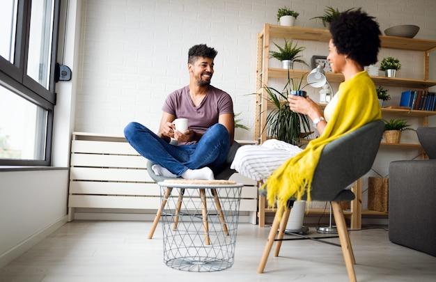 Gelukkig afrikaans amerikaans paar dat koffie drinkt in een gezellig huis. familie vrije tijd en ontspanning concept