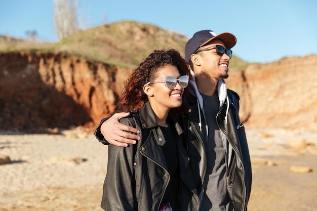 Gelukkig afrikaans houdend van paar dat in openlucht bij strand loopt