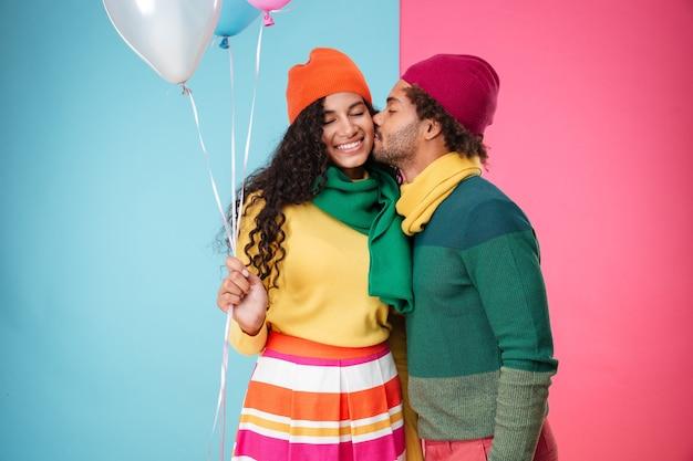 Gelukkig afrikaans jong stel in hoeden en sjaals met ballonnen knuffelen en zoenen