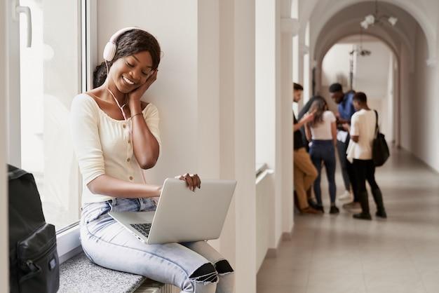 Gelukkig afrikaans meisje alleen zittend op de vensterbank en met behulp van laptop op pauze. vrij vrouwelijke student luisteren muziek van grote koptelefoon en kijken naar video's wanneer vrienden praten op de achtergrond.