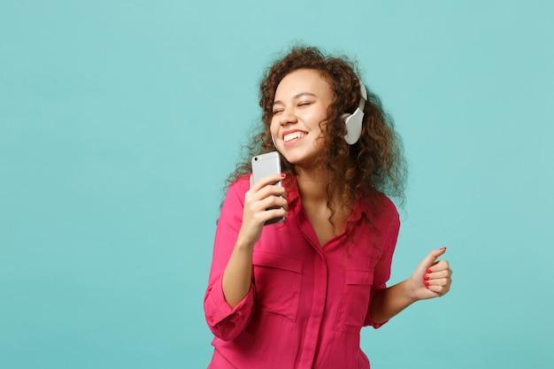 Gelukkig afrikaans meisje in casual kleding houdt mobiele telefoon vast, luistert muziek met koptelefoon geïsoleerd op blauwe turkooizen achtergrond in studio. mensen oprechte emoties levensstijl concept. bespotten kopie ruimte.