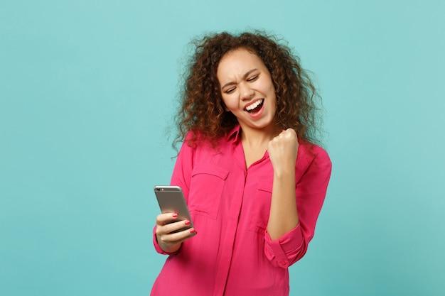 Gelukkig afrikaans meisje in casual kleding winnaar gebaar doen, met behulp van mobiele telefoon, sms-bericht typen geïsoleerd op blauwe turkooizen achtergrond. mensen oprechte emoties, lifestyle concept. bespotten kopie ruimte.