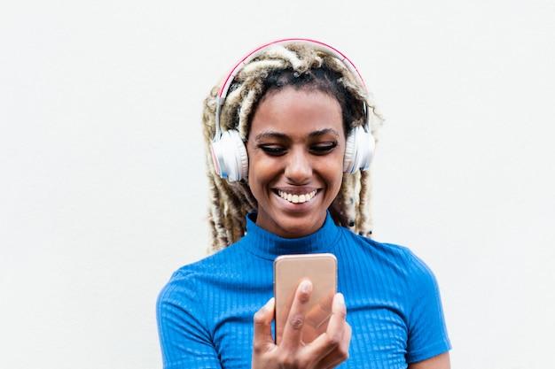 Gelukkig afrikaans meisje kijken naar video's en muziek luisteren met de mobiele telefoon-app