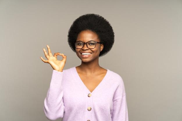 Gelukkig afrikaans meisje laat een goed gebaar zien, geef goed advies of help een tevreden bedrijf of servicecliënt