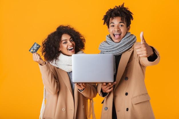 Gelukkig afrikaans paar dragen winterkleren permanent geïsoleerd, met laptop computer, plastic creditcard tonen, vieren