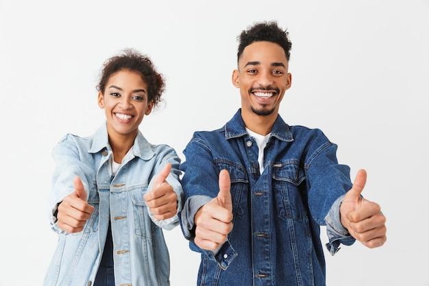 Gelukkig afrikaans paar in denimoverhemden die duimen over grijze muur tonen