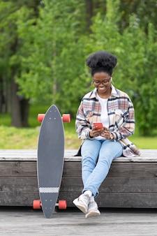 Gelukkig afrikaans skatermeisje dat online sms't in de smartphone-app zit met longboard op een bankje in het skatepark