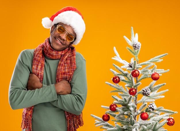 Gelukkig afrikaanse amerikaanse mens in santahoed en sjaal om hals met glimlach op gezicht die zich naast een kerstboom over oranje muur bevinden