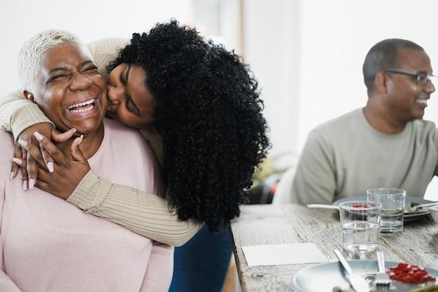 Gelukkig afrikaanse dochter met teder moment tijdens de lunch thuis