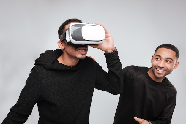 Gelukkig afrikaanse jonge mannen met behulp van 3d-virtual reality-apparaat.