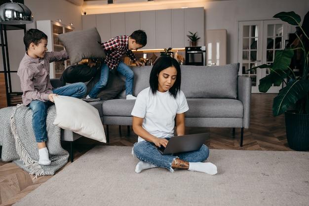 Gelukkig afrikaanse jonge moeder thuis werken met laptop en zich aanpassen aan actieve luidruchtige zonen vechten kussens op de bank