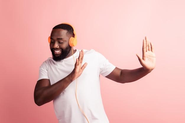 Gelukkig afrikaanse man die lacht luisteren naar muziek in koptelefoon stretch handen kant stopbord