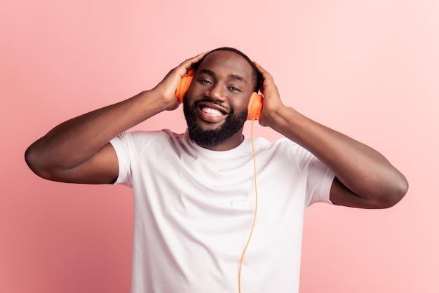 Gelukkig afrikaanse man luisteren naar muziek in koptelefoon brede glimlach op roze muur