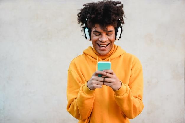 Gelukkig afrikaanse millennial man luisteren muziek afspeellijst met smartphone app buiten - jonge man met plezier met technologische trends - tech, generatie z en stijlvol concept - focus op gezicht