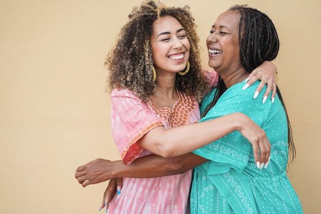 Gelukkig afrikaanse moeder en dochter knuffelen elkaar - liefde en familie concept