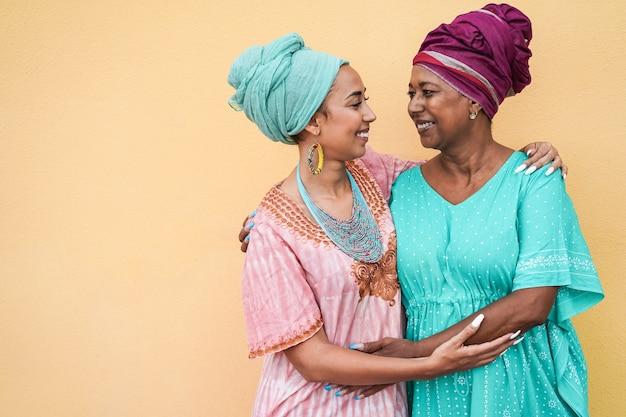 Gelukkig afrikaanse moeder en dochter knuffelen elkaar terwijl het dragen van traditionele jurken - focus op moeder gezicht