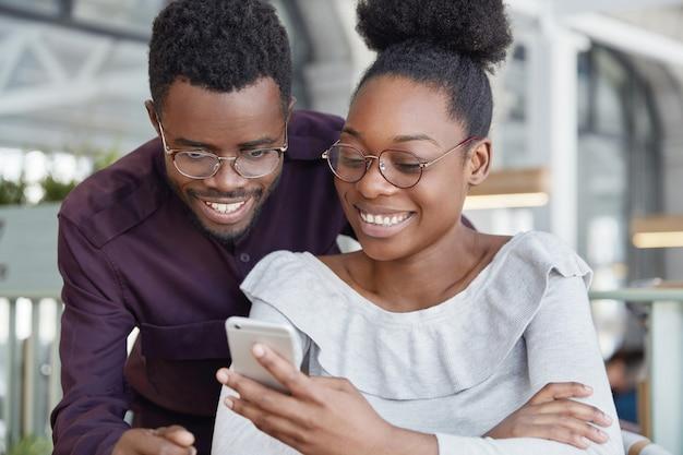 Gelukkig afrikaanse vrouw in bril typen bericht op moderne slimme telefoon terwijl haar vriendje in de buurt van haar staat en naar het scherm kijkt